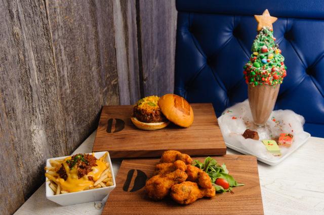 右奥にはクリスマスツリーを模したミルクシェイク。真ん中には長方形の木のお皿が2つあり、それぞれにバーガーとチキンが置かれている。左側には白い四角い器にチーズとミートが乗ったポテトが盛られている。