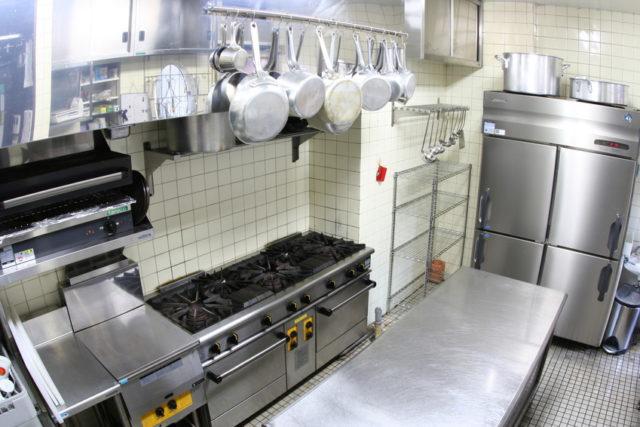 白い壁、白いタイルの厨房。奥には業務用の冷蔵庫が置かれ、コンロの上には様々な鍋がつるされている。