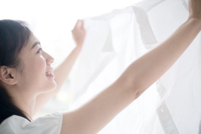 洗濯したブラウスを掲げる女性