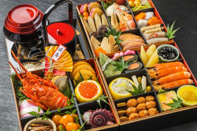 三段のお重が広げて置かれており、中には色とりどりのおせち料理が詰められている。