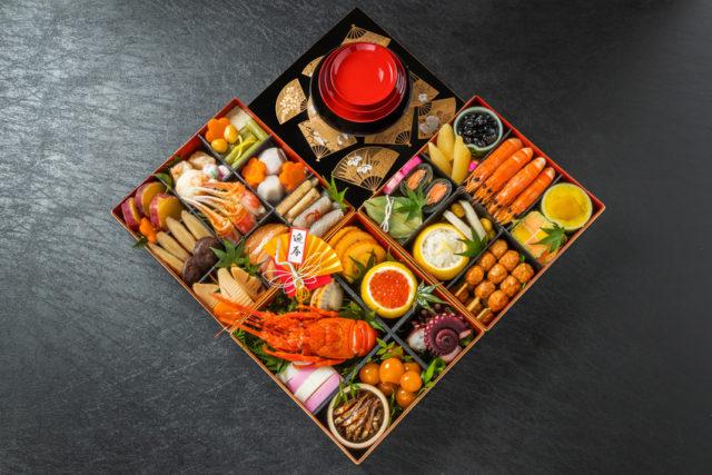 三段のお重が広げられており中にはおせち料理がきれいに入っている様子を真上から撮られた写真。