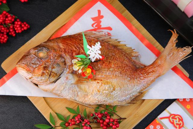 四角い木の器に寿と書かれた紅白の敷き紙が置かれ、その上に鯛が盛り付けられている写真。