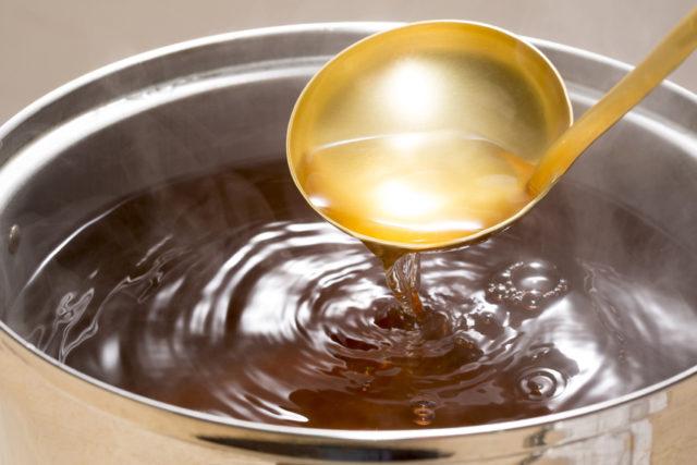 お鍋に美しく透き通った出汁が入っており、金色のお玉ですくっている様子