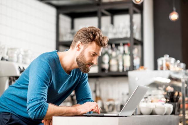 青い服を着た男性がパソコンを見ながら不穏な表情を浮かべている写真
