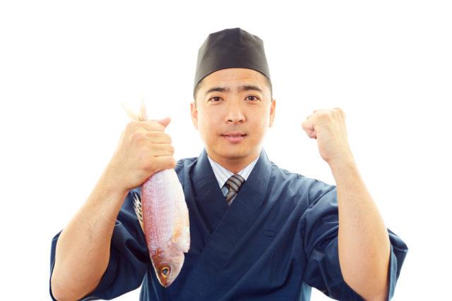 右手に魚を持った笑顔の寿司職人の男性。