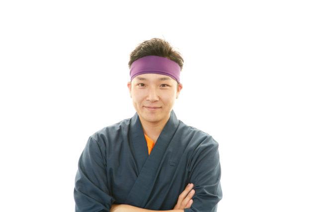 頭に紫色のハチマキをした寿司職人の男性