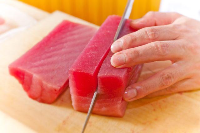 まな板の上で魚のブロックを包丁で切り付けている