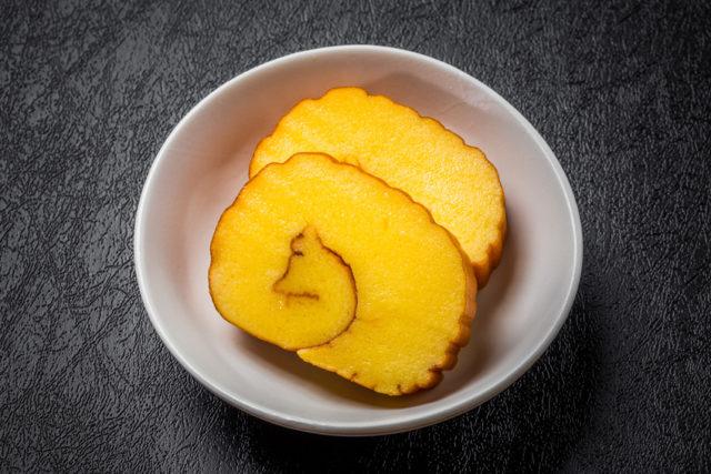 白い小皿に黄色が鮮やかな伊達巻が盛られている写真