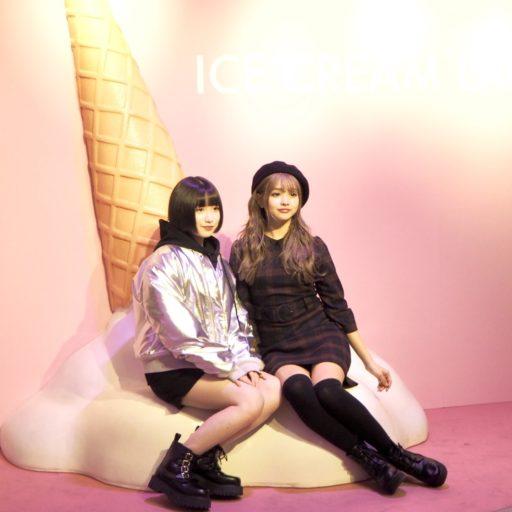 ピンクの部屋にアイスクリームのオブジェが置かれており、そこに女の子2人が座っている写真