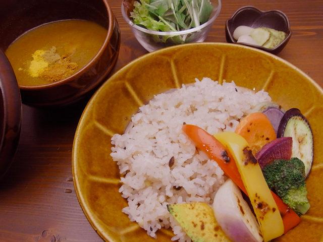 市いろいお皿に色とりどりの野菜とごはん、隣のお椀にカレーが盛り付けられている写真