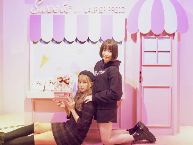 ピンクと白色のお店を模したブースで黒ベースの服を着た女の子2人が雑誌をもってポージングしている写真