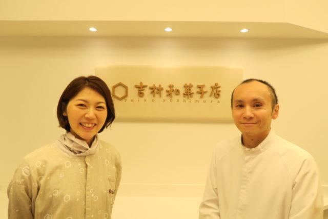 吉村和菓子店の看板の前に笑顔の夫婦が経っている写真