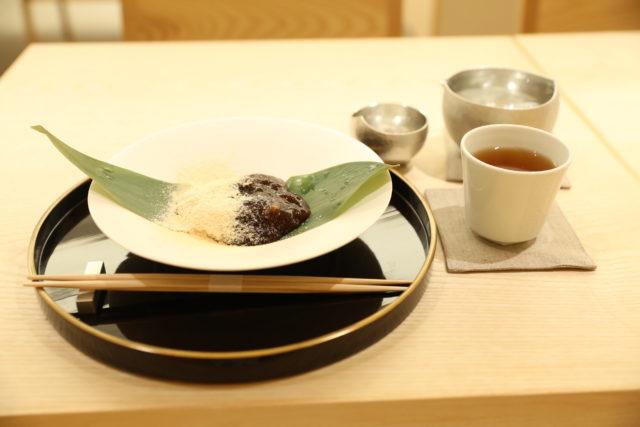 黒のお盆の上に餡のかかったわらび餅が盛り付けられ、傍らにはほうじ茶が置かれた写真