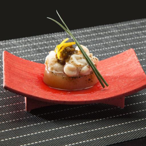赤い湾曲した資格の皿の上に和食が盛り付けられている写真