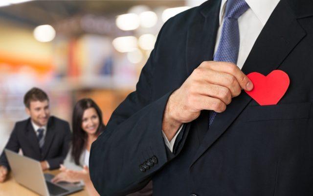 スーツの胸ポケットから赤いハートを取り出している写真