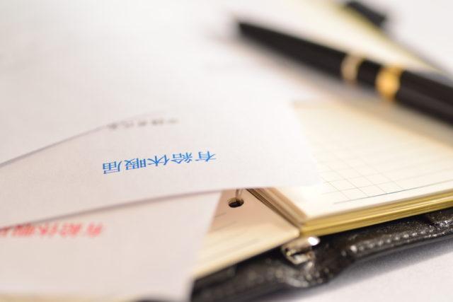 ノートの上に「有休休暇届」と書かれた紙が置かれている写真