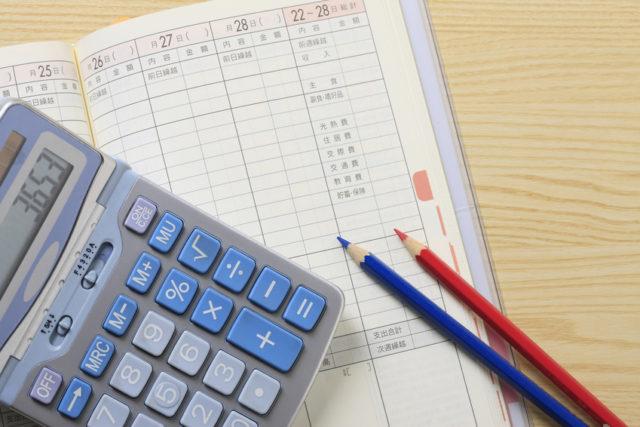 家計簿の上に電卓と赤青の鉛筆が置かれている写真
