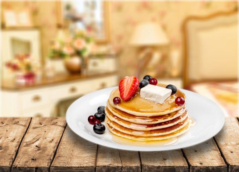 木のベンチの上に白い丸皿に乗ったパンケーキの写真