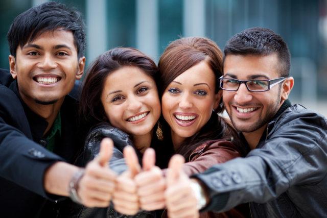 男女4人の外国人が肩を寄せ合いグッドにした手を突き出している写真