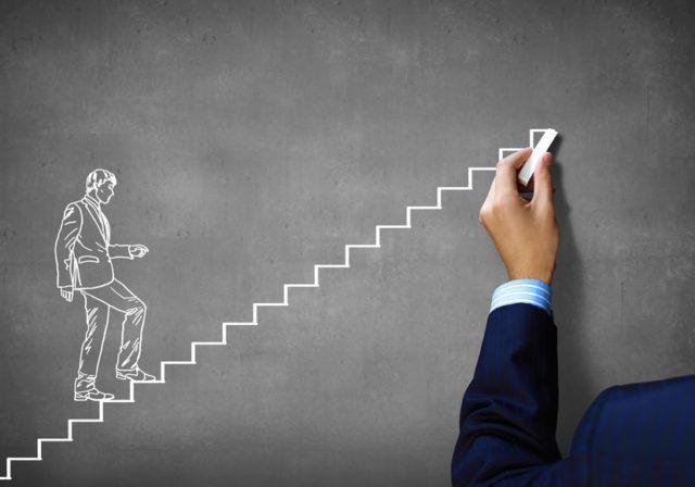 黒板に男性が階段を上っている様子がチョークで描かれている写真