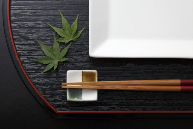 黒いお盆の上に四角い皿と四角い箸置きに置かれたお箸、モミジが飾られている写真
