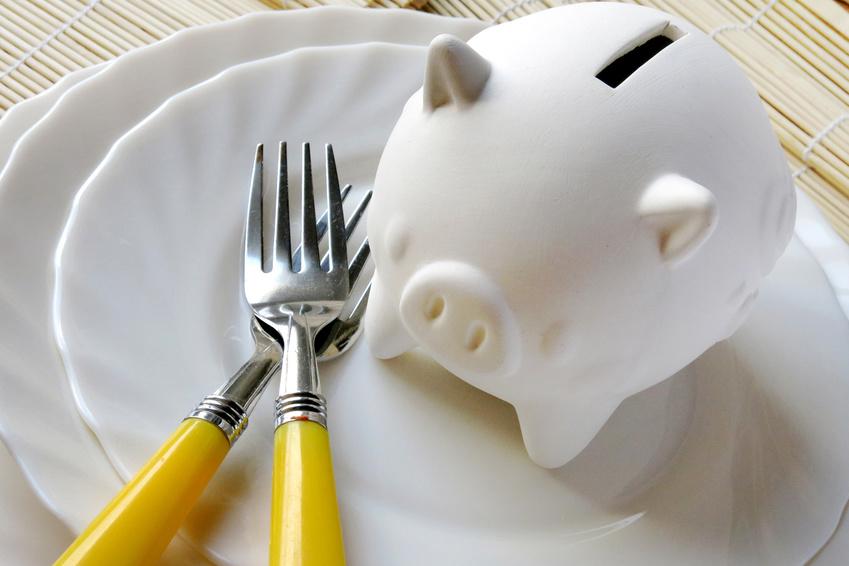 お皿の上に白い豚の貯金箱と黄色い取っ手のフォークが2本置かれている写真