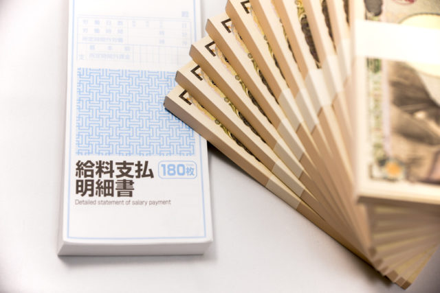 扇状に積み上げられた札束と給料支払明細書が置かれた写真