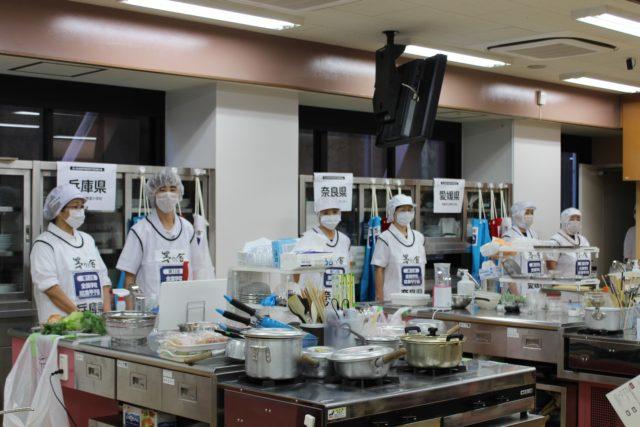 調理台の上にお鍋やフライパンなどの調理器具が山盛りに置かれており、その後ろに給食キャップにマスク姿の選手たちが経っている写真