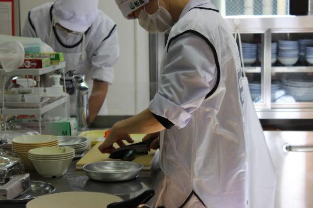 まな板の上で食材を切っている白い調理服姿の選手