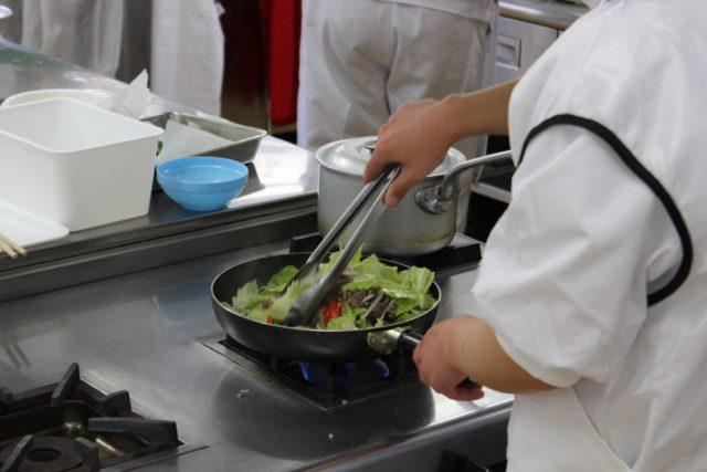 コンロの上のフライパンの中には野菜がたくさん入っており、トングを使って調理している選手の手元の写真