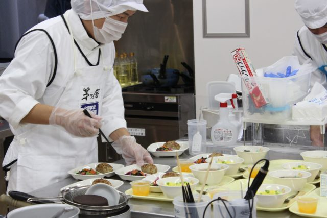 トレイに完成した料理を並べている白衣姿の選手