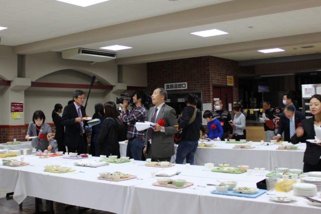 白いクロスのかけられたテーブルの上に置かれたお盆に盛られた給食。その周りを審査員やマスコミが囲んでいる写真