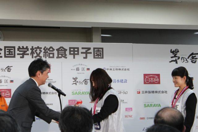 「全国学校給食甲子園®」の前で表彰されている女性選手の写真