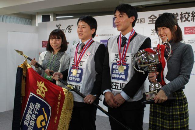 優勝旗とトロフィーを持つ男性2名、女性2名の写真
