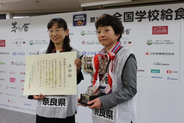 「全国学校給食甲子園®」の前で表彰状とトロフィーを持つ2人の女性選手の写真