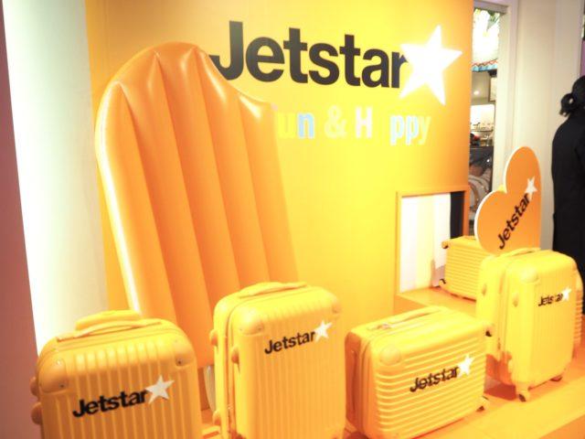 黄色一色のスーツケースやフロート浮き輪がディスプレイされた「Jetstar」のブースの写真