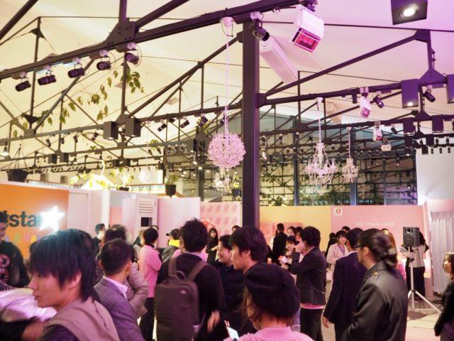 ピンク色の照明がたかれた会場内にはたくさんの人が集まっている様子の写真