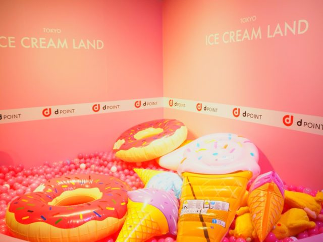 ピンクの壁紙にピンクのボールプールが置かれ、そこにスイーツの巨大クッションが置かれている写真