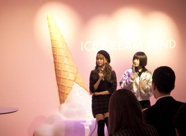 ピンクの壁に巨大なアイスクリームのオブジェが施してあり、その前で2人の女の子がマイクをもっている様子