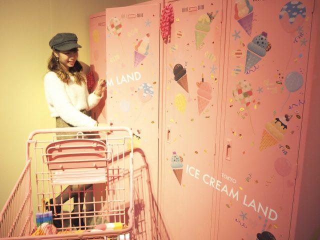 ピンクのショッピングカートとカラフルなアイスクリームの絵が描かれているピンクのロッカーにが置かれ、黒いハンチング帽をかぶった女の子がそのロッカーを開けておる写真
