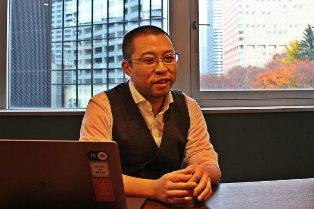 窓際の茶色いテーブルの上にはノートパソコンが開かれており、そこに眼鏡に短髪の高梨社長が座っている写真