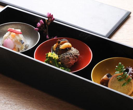 黒長方形の箱の中に3つの小皿が置かれそれぞれに料理が盛られている写真