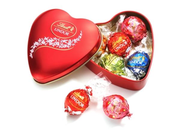 赤いハート型のケースに赤、青、ピンク、黄緑のラッピングが施されたチョコレートが入っている写真