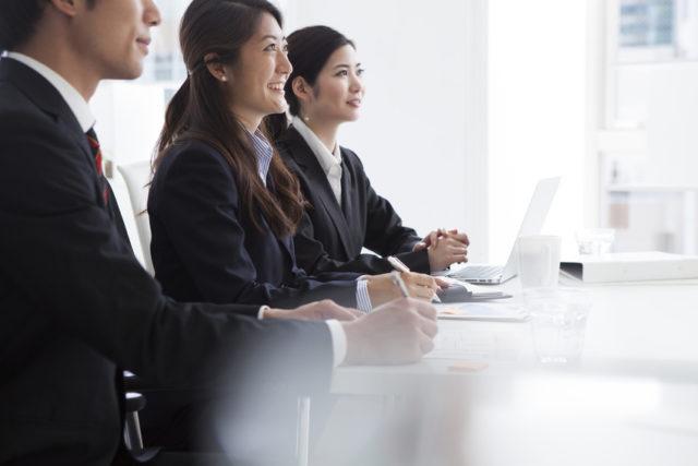スーツ姿の男女3人が同じ方向を向いて横並びに座って、笑顔でメモを取っている様子の写真