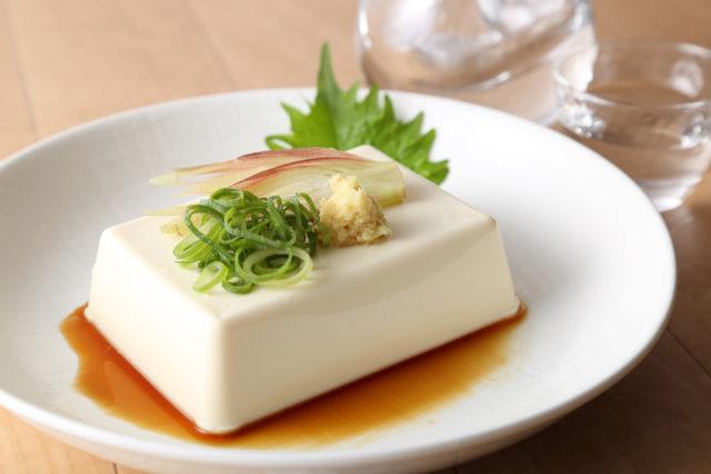 白い丸皿にネギと生姜とミョウガが乗った豆腐が盛り付けられている写真