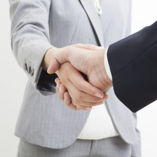 グレーのスーツの人と黒のスーツの人が握手している写真