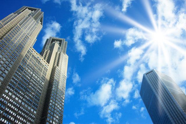 青空にが写された下から都庁を見上げたような写真