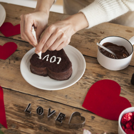 木のテーブルの上でハート型のチョコレートにLOVEと書いている様子の写真