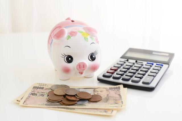 電卓と豚の貯金箱の前にお金が置かれている写真