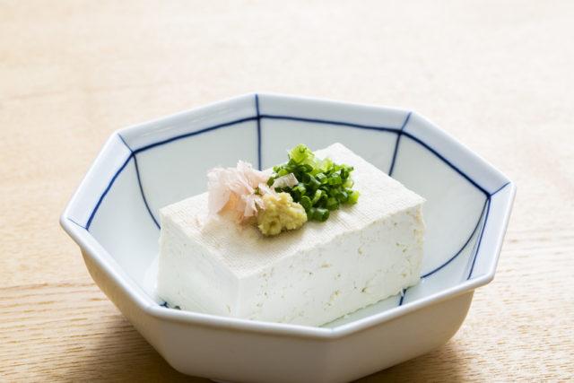 八角形の器に鰹節、生姜、ネギが盛り付けられた豆腐が盛り付けられている写真